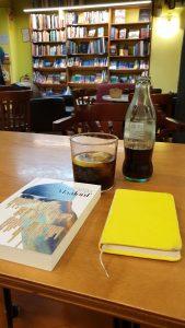 Mesa preparada con libro, libreta y refresco